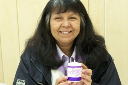 Community member with a Purple Ribbon Campaign decorated candle.