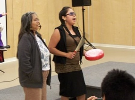 Community members offer an honour song to all women.