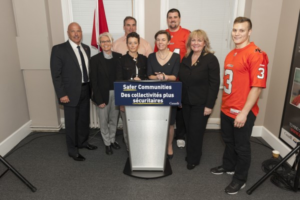 The Honourable Dr. K. Kellie Leitch, along with the Honourable Kerry-Lynne D. Findlay, George Chayka, Jamie Taras, Matt McGarva and Dean Valli from the BC Lions, Inspector Cita Airth from the VPD and EVA BC's Executive Director Tracy Porteous after the announcement of a new call for proposals for projects to end violence against women and girls.